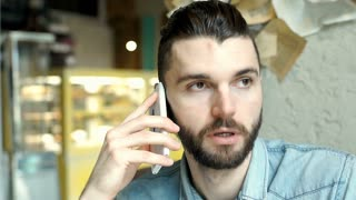 Handsome man speaking with someone on cellphone and making faces