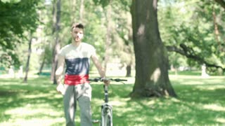 Handsome man walking with bicycle in the park and doing selfies on smartphone, s