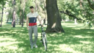 Handsome man walking with the bicycle in the park and smiling to the camera, ste