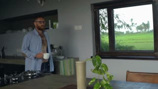 Handsome man walking with the coffee in the flat, steadycam shot, slow motion sh