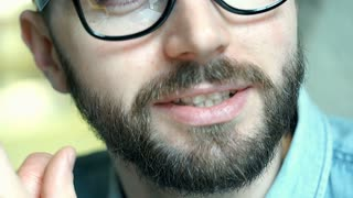 Handsome man wearing glasses and looks very happy, close up, steadycam shot