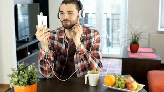 Handsome man wearing headphones and having a videocall on smartphone, steadycam