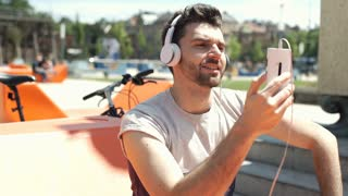 Handsome man wearing headphones and having a videochat on smartphone in the city
