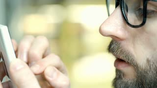 Handsome man with glasses browsing internet on smartphone, close up, steadycam s