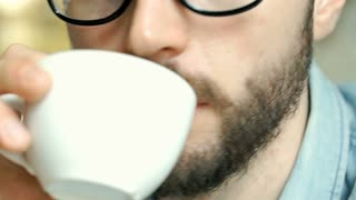 Handsome man with glasses drinking coffee, close up, steadycam shot