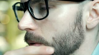 Handsome man with glasses looks very worried, close up, steadycam shot