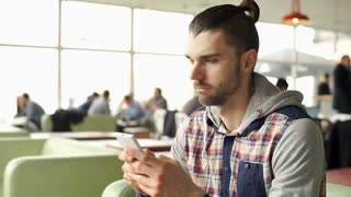 Handsome man with mud bun wearing hoodie and texting on smartphone in the cafe,
