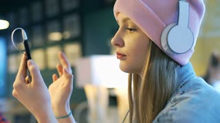 Happy, blonde girl in pink beanie is listening music and browsing internet on sm