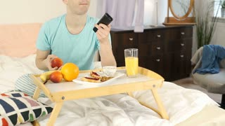 Happy boy having breakfast in bed and watching television at the morning, steady