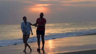 Happy couple walking on the beach during sunset, steadycam shot, slow motion sho