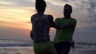 Happy cuple going round on the beach during sunset, steadycam shot, slow motion