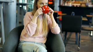 Happy girl drinking coffee from vintage mug and texting on smartphone, steadycam