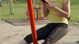 Happy girl exercising on the playground and texting on smartphone, steadycam sho