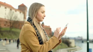 Happy girl in stylish, honey coat standing on boulevards and using smartphone, s
