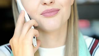 Happy girl with beautiful, natural makeup chatting on cellphone