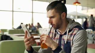 Happy man drinking orange juice and watching something funny on tablet, steadyca