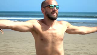 Happy man holding pink shirt and going round on the beach, slow motion shot at 2