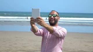 Happy man standing on the beach and recording view on tablet, slow motion shot a