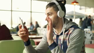 Happy man wearing headphones and having a videocall on smartphone, steadycam sho
