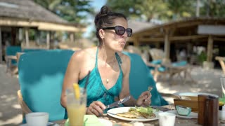 Happy woman eating delicious lunch on the tropical island, steadycam shot
