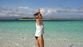 Happy woman raising hands and spinning around on idyllic beach, slomotion