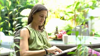 Happy woman sitting outdoors and using notebook, steadycam shot
