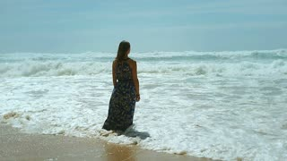 Happy woman standing in the sea and getting wet, steadycam shot