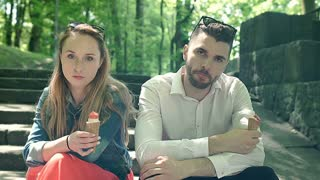 Irritated couple looking to the camera and eating ice creams, steadycam shot
