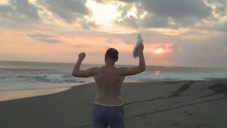 Joyful man standing on the beach and waving with a shirt, steadycam shot, slow m