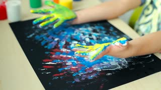 Kid having his hands in colorful paint and doing marks on black paper