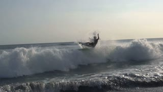 Man falls off from the wave while surfing, steadycam shot, slow motion shot at 2