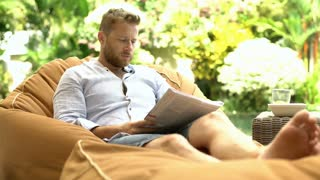 Man feels hot while sitting on the bean bag chair and cooling himself down with
