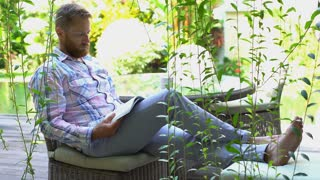Man finishes reading book and relaxing in the garden