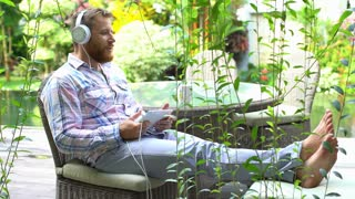 Man having fun while relaxing in the garden and listening music