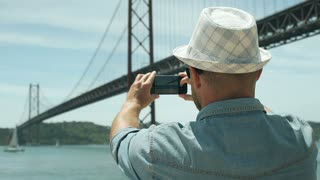 Man holding smartphone and captures the view on it, steadycam shot