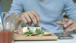 Man in blue sweater eating lunch and browsing internet on smartphone, steadycam