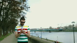 Man in colorful shirt listening music on boulevards and smiling to the camera, s