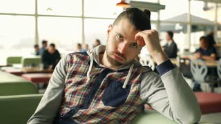 Man in hoodie having problems and looks worried while sitting in the cafe, stead