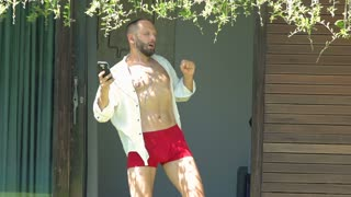 Man in red pants dancing outside and dancing while listening music, steadycam shot, slow motion shot at 240fps