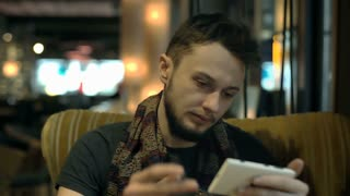 Man look tired while sitting in the dark cafe and browsing internet on smartphon