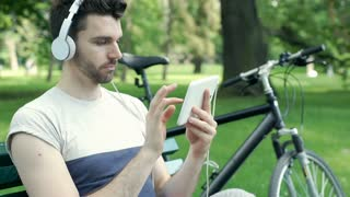 Man looks bored while listening music and browsing internet on tablet in the par