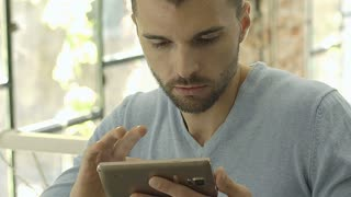 Man looks shocked while browsing internet on smartphone, steadycam shot