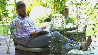 Man relaxing in the garden and reading some publication