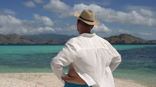Man relaxing on the beautiful beach, steadycam shot, slow motion shot at 240fps