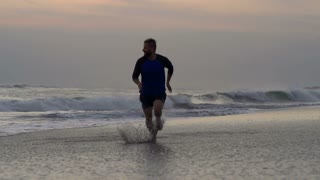 Man running on the beach and splashing water, steadycam shot, slow motion shot a