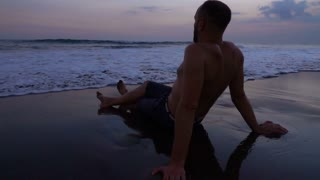 Man sitting on the beach and waves splashing on him, slow motion shot at 240fps,