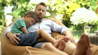 Man sitting with his son on the bean bag chair and relaxing during their holiday
