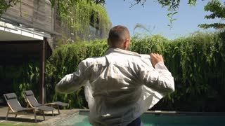 Man standing in the garden and puts shirt on, steadycam shot, slow motion shot a