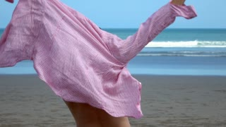 Man standing on the beach and wearing pink shirt, slow motion shot at 240fps, st
