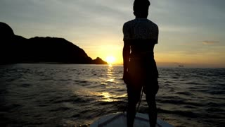 Man standing on the ship's bow and admires the sunset, slow motion shot at 240fp